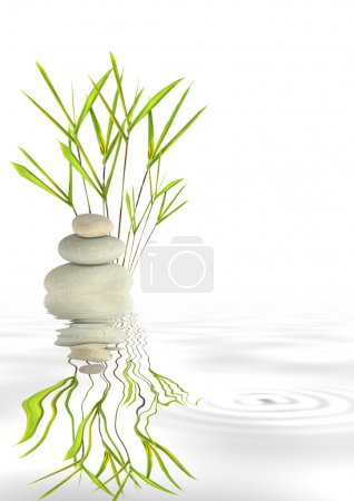 Photo for Zen abstract of spa massage stones in perfect balance with reflection over rippled grey water. Against white background. - Royalty Free Image
