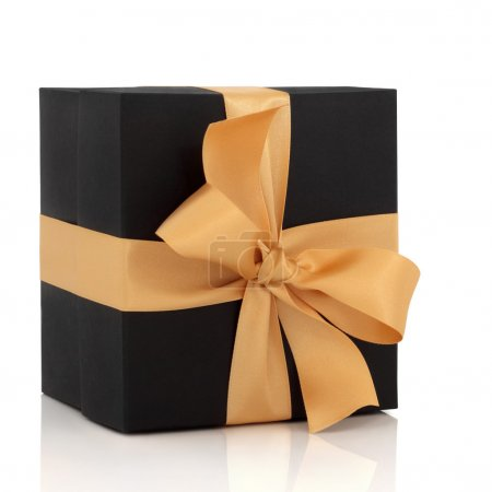 Photo for Black gift box with gold satin ribbon and large bow, isolated over white background with reflection. - Royalty Free Image