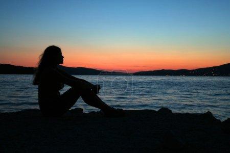 Photo pour Femme sexy assis sur la plage pendant le coucher du soleil - image libre de droit