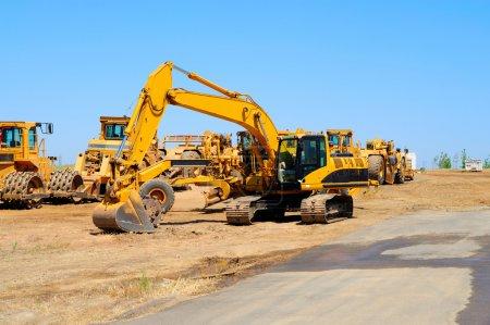 Photo pour L'équipement lourd de construction est au ralenti aligné le long d'une nouvelle route asphaltée - image libre de droit