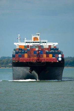 Photo pour Bateau porte-conteneurs complètement chargé frontalement en eau calme - image libre de droit