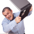 Angry businessman smashing his laptop on the table...