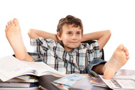Photo pour Portrait d'un écolier pieds nus les pieds sur son bureau, attendant les vacances à venir - image libre de droit