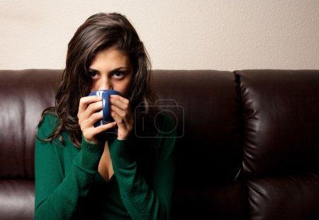 Beautiful brunette having tea or coffee