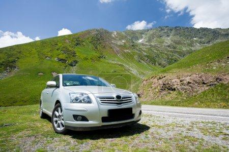 Car parked near a road through mountains