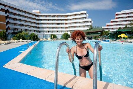 Photo pour Jolie rousse jeune femme dans une piscine près d'un hôtel - image libre de droit