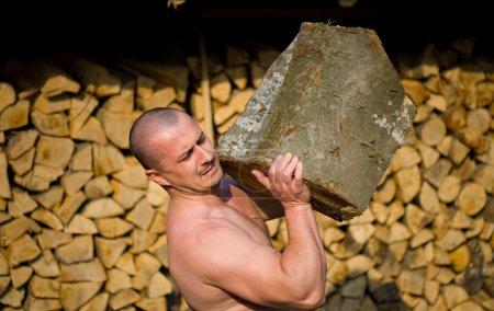 Photo pour Homme fort soulevant une énorme bûche, scène extérieure - image libre de droit