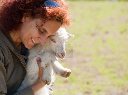 Photo pour Jeune femme avec un bébé chèvre très mignon - image libre de droit