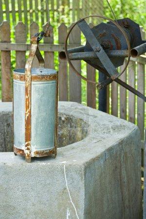 Photo pour Vieux puits avec un seau en métal - image libre de droit