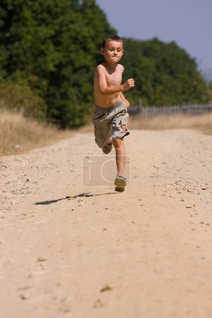Photo for Seven year old kid running on a dusty road in the countryside - Royalty Free Image