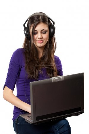 Photo pour Young brunette lady sitting on a chair with headphones connected to laptop - image libre de droit