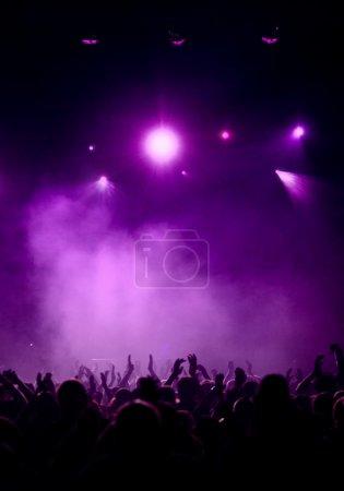 Photo pour Silhouette de foule acclamant levant les mains, fond violet avec éclairage de concert atmosphérique - image libre de droit