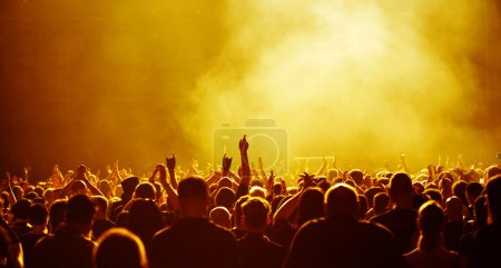 Photo for Cheering concert audience or party crowd raising hands, yellow light - Royalty Free Image