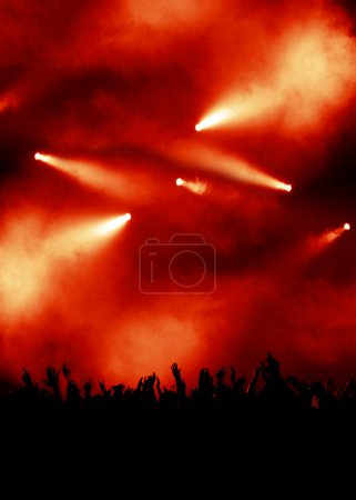 Photo pour Silhouette des acclamations de la foule levant les mains, fond rouge avec éclairage dramatique concert rouge - image libre de droit
