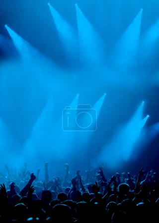 Photo for Silhouette of cheering crowd raising hands, cyan blue background with dramatic concert lighting - Royalty Free Image