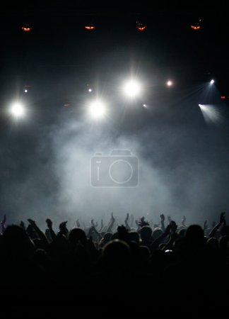 Photo for Silhouette of concert audience or party crowd, fans raising arms in blueish light - Royalty Free Image