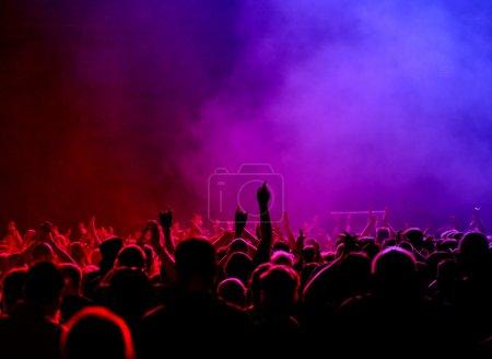 Photo pour Concert public ou parti foule levant mains, lumière rouge-rose-bleu-violet - image libre de droit