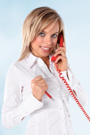 Young blond girl talking on a telephone