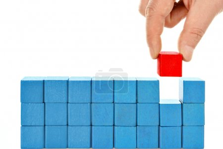 Photo for Child hand make a building of colored blocks isolated on white - Royalty Free Image