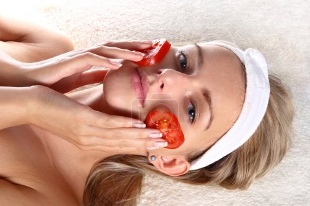 Woman with fresh tomatoes mask