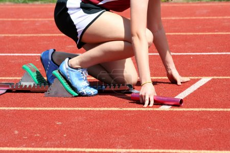 Photo for Runner in the starting blocks with baton - Royalty Free Image