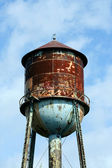 Old rusty watertower against blue sky