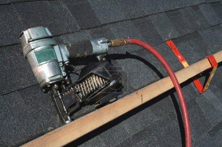 Photo pour Une toiture pneumatique nail gun avec tuyau d'air - image libre de droit