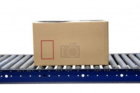 Photo pour Carton isolé sur rouleaux de convoyeur dans un entrepôt - image libre de droit