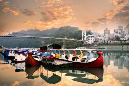 Photo for Color boats on river with buildings and bridge. - Royalty Free Image