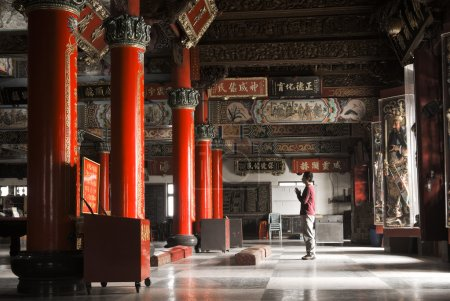 Photo for Building interior of temple with one Asian prayer begging and standing. - Royalty Free Image