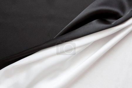 Photo pour Le beau tissu ondulé noir et blanc brillant et soyeux coupé en deux - image libre de droit