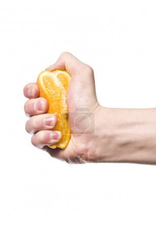Photo for Hand squeezing an orange towards white background - Royalty Free Image