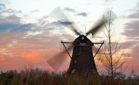 Windmills at windy sunset
