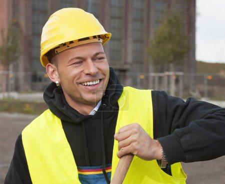 Photo pour Travailleur de la construction souriant en casque jaune - image libre de droit