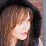 A woman model in a black hood looking away....