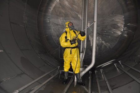 Photo for Man in chemical suit inside of cargo tank on chemical tanker for cleaning operation - Royalty Free Image