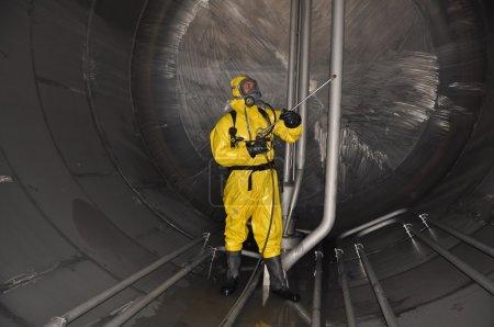 Foto de Hombre en traje químico dentro del tanque de carga de cisterna para productos químicos para la limpieza - Imagen libre de derechos