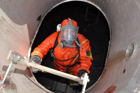 Photo for Man in chemical suit entering inside cargo tank on chemical ship for cleaning operation - Royalty Free Image
