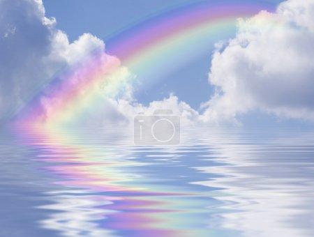 Photo pour Arc-en-ciel coloré sur ciel bleu avec nuages et réflexion sur l'eau - image libre de droit