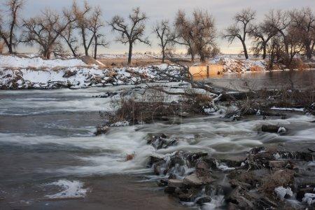 Photo pour L'un des nombreux barrages sur la rivière South Platte dans le Colorado détournant l'eau pour l'irrigation des terres agricoles, porte d'entrée des fossés, paysages hivernaux - image libre de droit