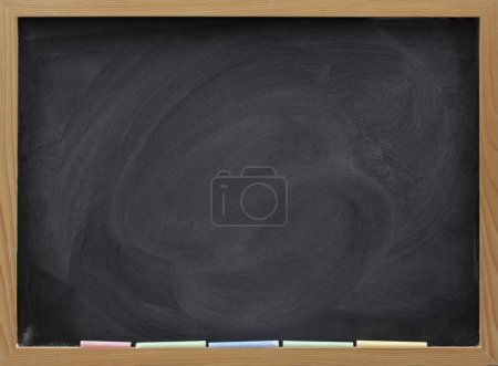 Photo for Blank blackboard in wooden frame, colorful chalk sticks, and eraser smudges - Royalty Free Image