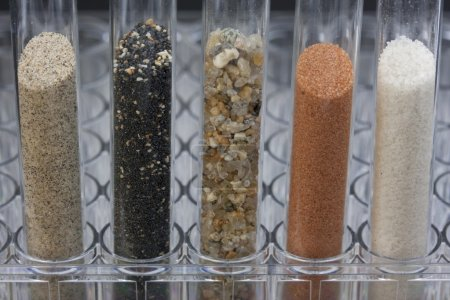 Five glass testing tubes with different sand sampl...