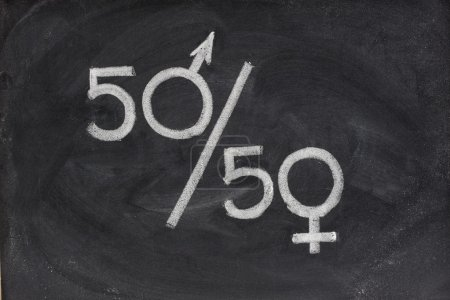Photo pour Cinquante pour cent - concept d'égalité des chances entre les sexes ou de représentation dans la vie politique et publique esquissé à la craie blanche sur le tableau noir - image libre de droit