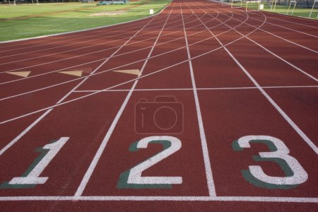 Photo for Red running track with 1, 2, 3 numbers at the starting line and green fields - Royalty Free Image