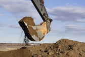 Excavator arm and scoop digging dirt