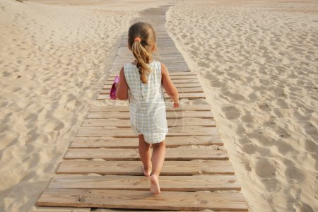Photo for The barefooted little girl goes on board road among sand - Royalty Free Image