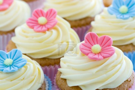 Cupcakes decorated with frosting and sugar flowers...