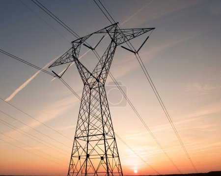 Photo for Electric power pylon and wires silhouetted by a colorful sunset. - Royalty Free Image