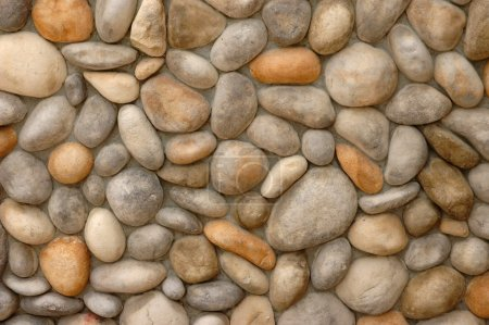 Photo pour Mur décoré de gros cailloux frittés ensemble - image libre de droit