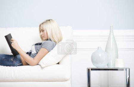 Foto de Joven lleva una blusa a cuadros y pantalones vaqueros azules, acostado en el sofá blanco y libro de lectura. hoizontal tiro. - Imagen libre de derechos